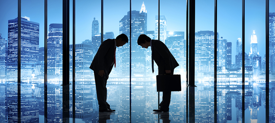Two Businessmen Bowing To Each Other In An Office Building